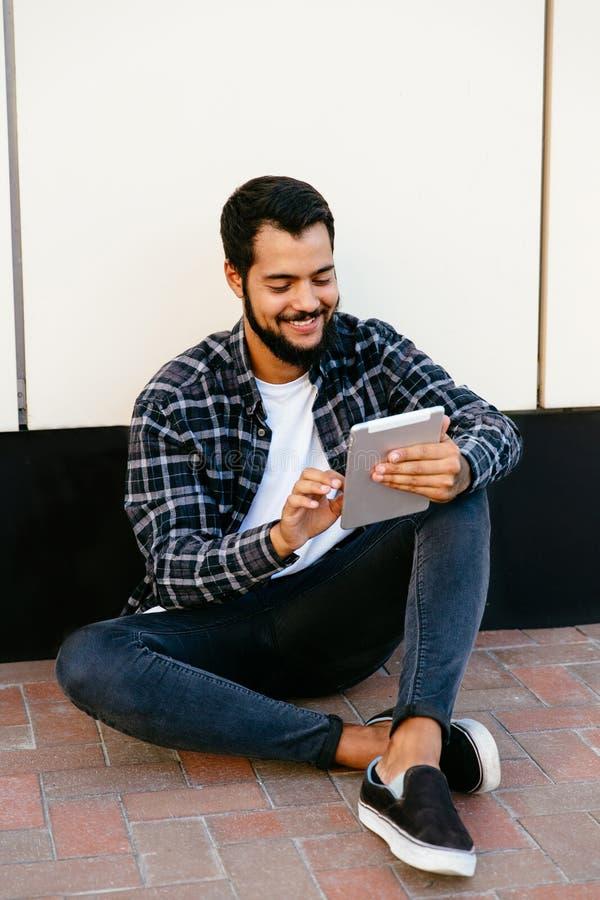 Glimlachende gebaarde mens die een computertablet gebruiken terwijl het zitten dichtbij de muur, in openlucht stock fotografie