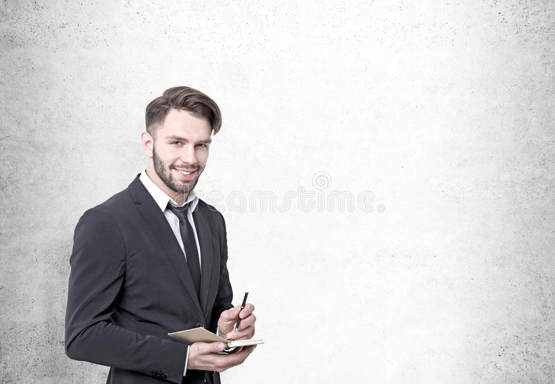 Glimlachende gebaarde zakenman, concrete muur royalty-vrije stock afbeelding