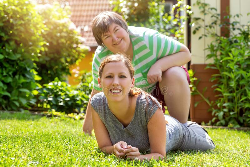 Glimlachende geestelijke gehandicapte vrouw en een vriend in de tuin royalty-vrije stock fotografie