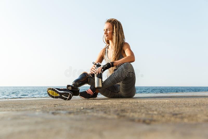 Glimlachende gehandicapte atletenvrouw met prothetisch been royalty-vrije stock fotografie