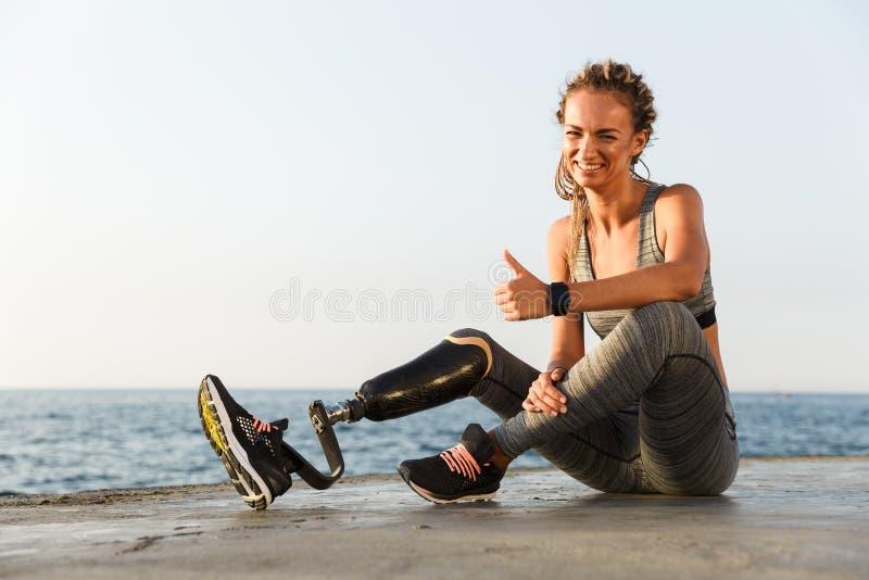 Glimlachende gehandicapte atletenvrouw met prothetisch been stock fotografie