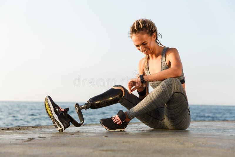 Glimlachende gehandicapte atletenvrouw met prothetisch been stock afbeelding