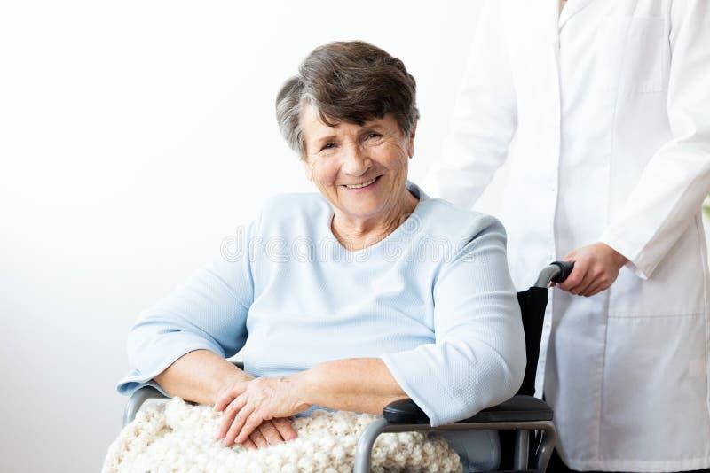 Glimlachende gehandicapte hogere vrouw in een rolstoel in verzorgingshou stock foto