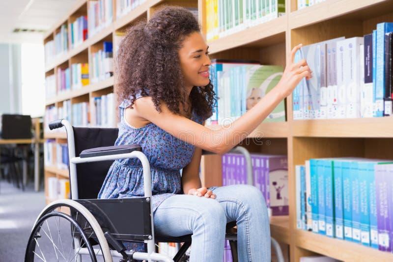 Glimlachende gehandicapte student in bibliotheek het plukken boek stock foto's