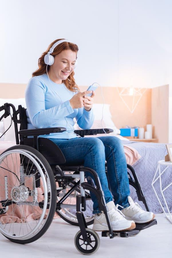 Glimlachende gehandicapte vrouw die hoofdtelefoon en het gebruiken van haar telefoon dragen stock fotografie