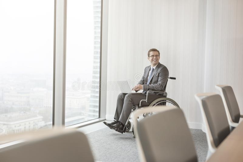 Glimlachende gehandicapte zakenman met laptop in bestuurskamer op modern kantoor stock foto's