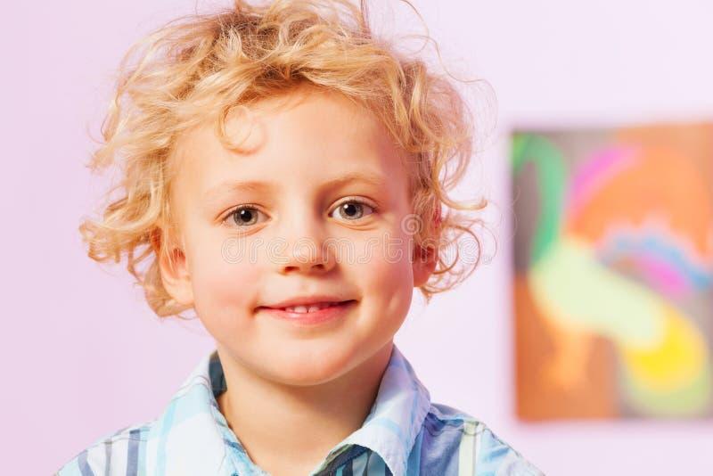 Glimlachende gelukkige blonde jongen met krullend haar stock fotografie