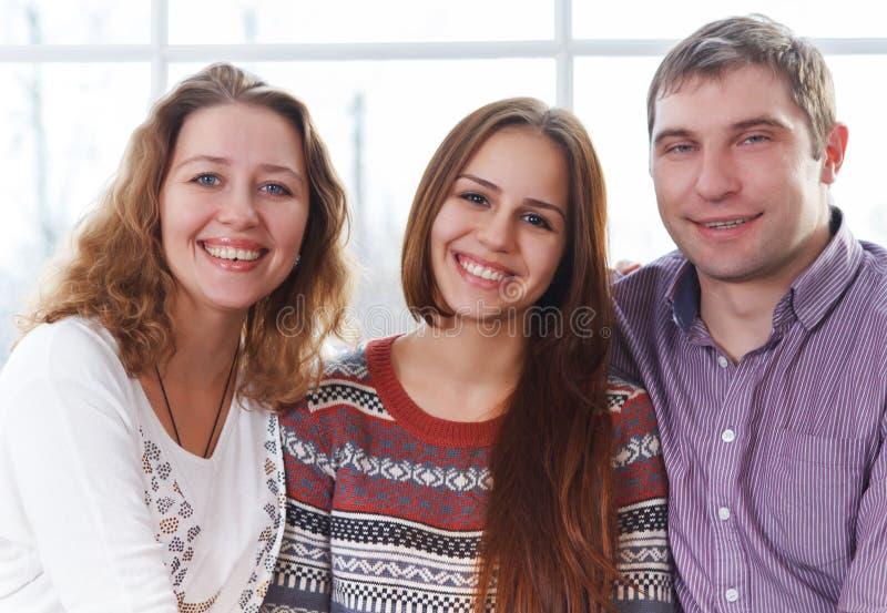 Glimlachende gelukkige familie met tienerdochter stock afbeelding