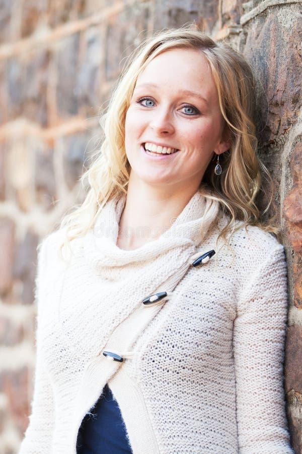Glimlachende gelukkige jonge blondevrouw naast natuursteenmuur stock foto's