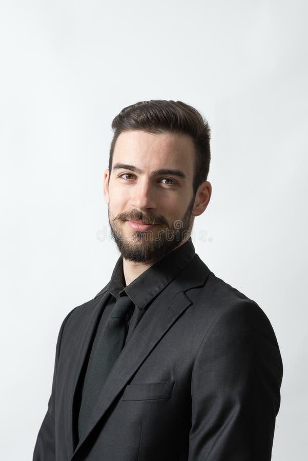 Glimlachende gelukkige jonge gebaarde elegante mens in zwart kostuum stock fotografie