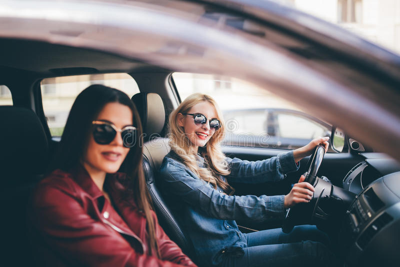 Glimlachende gelukkige jonge vrouw die haar vriend een lift in haar auto in stad, profielmening door het open zijruit geven royalty-vrije stock foto's