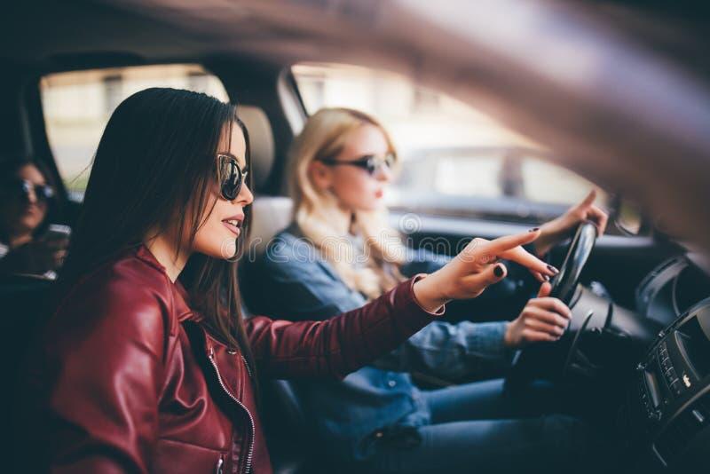 Glimlachende gelukkige jonge vrouw die haar vriend een lift in haar auto in stad, profielmening door het open zijruit geven stock foto