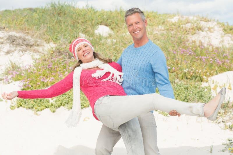 Glimlachende gelukkige man die een vrouw vervoeren royalty-vrije stock foto's