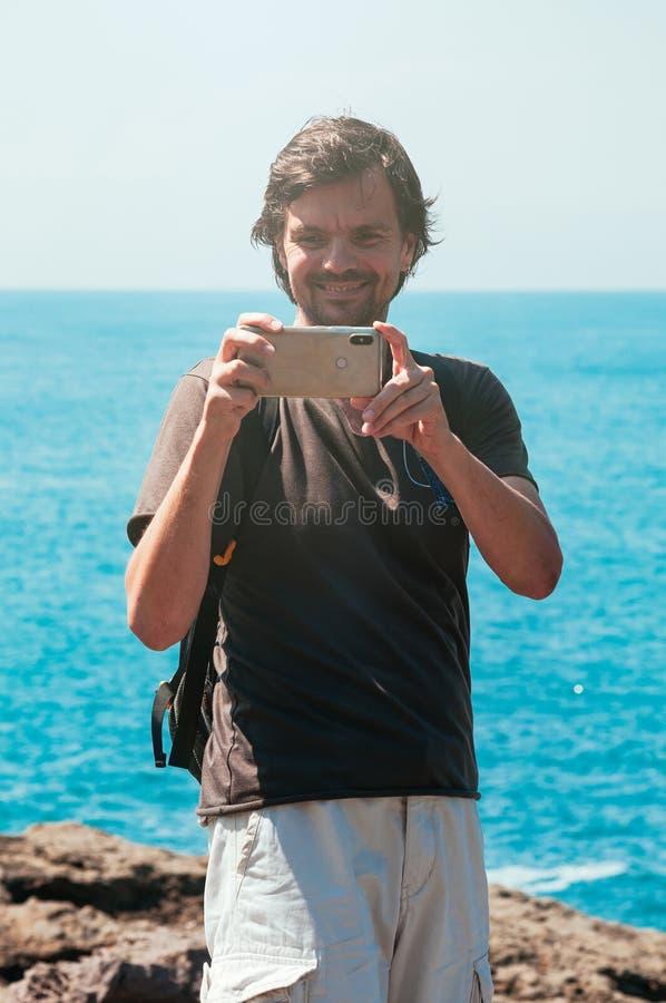 Glimlachende gelukkige mens, die foto nemen tegen blauwe overzees royalty-vrije stock foto's