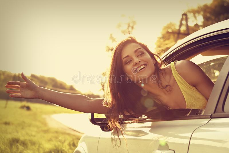 Glimlachende gelukkige reizende jonge vrouw die van de nieuwe autowinst kijken stock foto