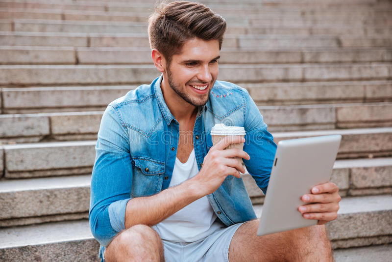 Glimlachende gelukkige toevallige mens gebruikend PC-tablet en drinkend koffie stock fotografie