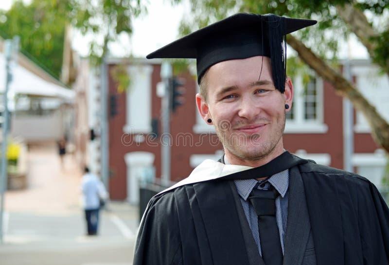 Glimlachende gelukkige universitaire gegradueerde jonge Kaukasische mens royalty-vrije stock afbeelding
