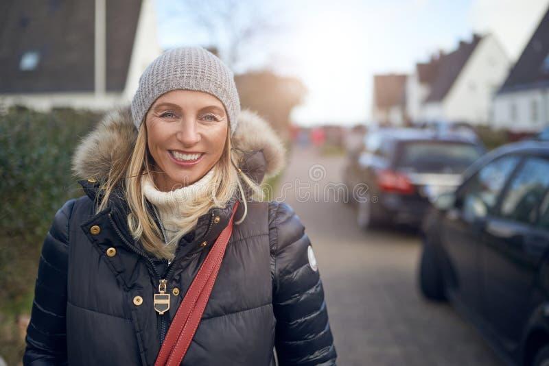 Glimlachende gelukkige vrouw die op middelbare leeftijd zich in openlucht bevinden stock foto's