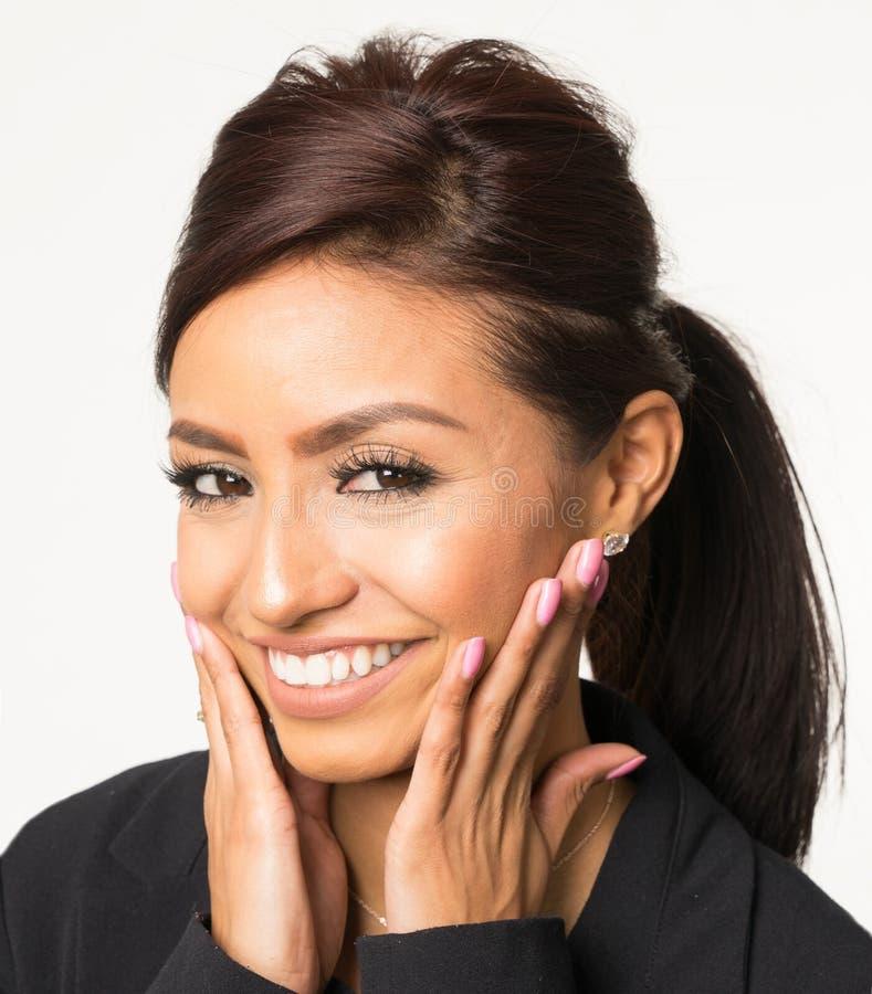 Glimlachende gelukkige vrouw met handen op gezicht stock fotografie