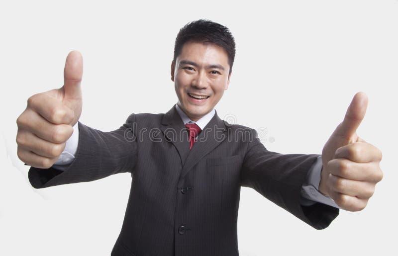 Glimlachende gelukkige zakenman die duim-omhoog met beide handen aan de camera, studioschot geven royalty-vrije stock fotografie