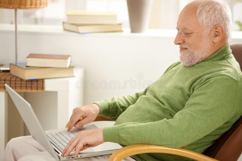 Glimlachende gepensioneerde die laptop computer met behulp van royalty-vrije stock afbeelding