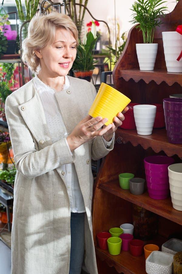 Glimlachende gepensioneerden vrouwelijke klant die bloempot kiezen stock afbeeldingen