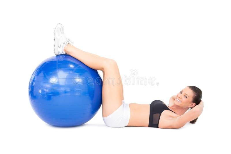 Glimlachende geschikte vrouw die haar abs ontwikkelen die oefeningsbal gebruiken stock afbeelding