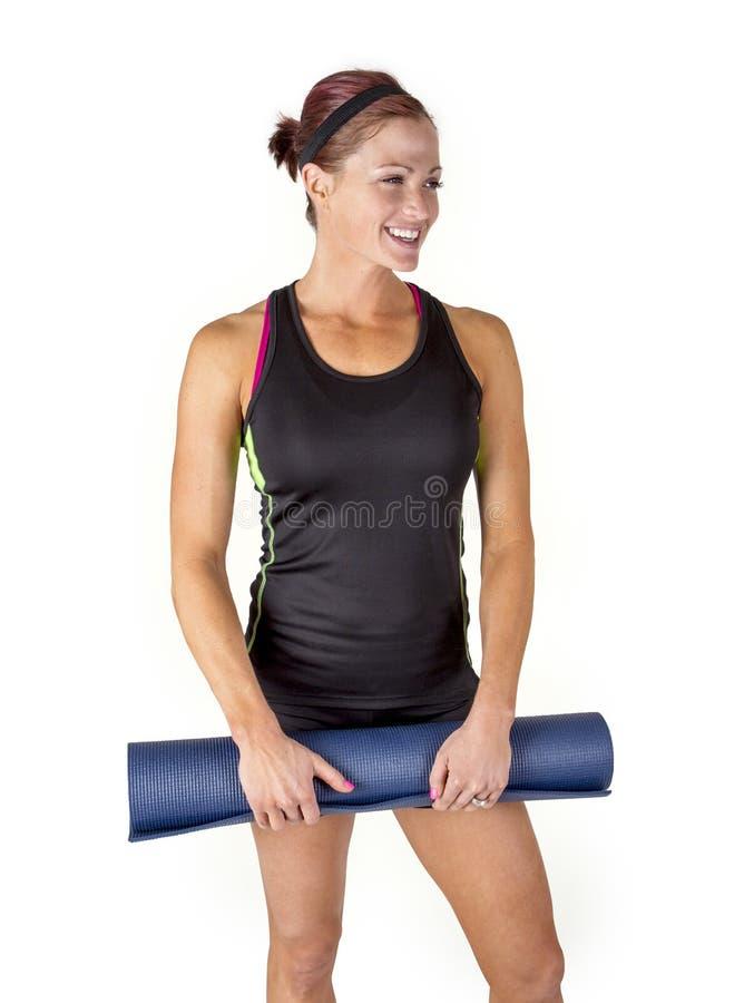 Glimlachende Geschikte vrouw die haar oefeningsmat houdt stock foto