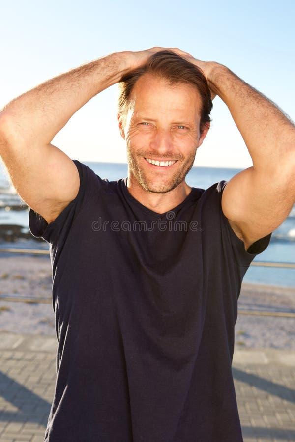 Glimlachende geschiktheidsmens met handen achter hoofd royalty-vrije stock fotografie