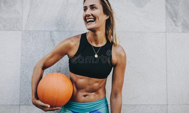 Glimlachende geschiktheidsvrouw die een basketbal houden stock fotografie