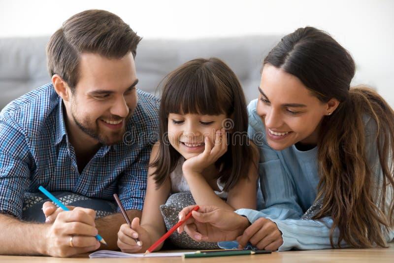 Glimlachende gevende ouders en de leuke tekening van de kinddochter met penc royalty-vrije stock fotografie