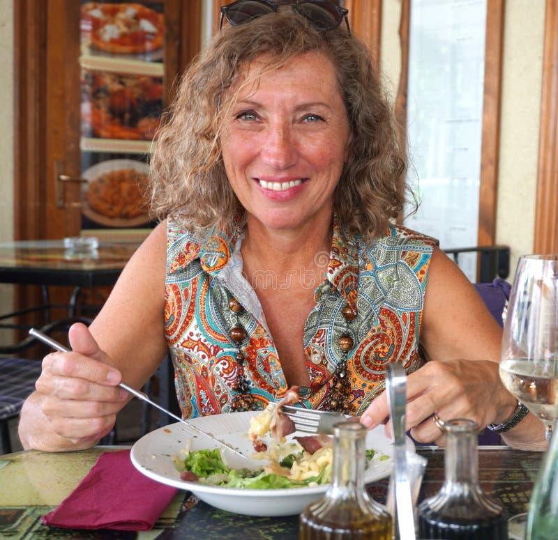 Glimlachende, gezonde en tevreden rijpe vrouw die in het restaurant eten royalty-vrije stock foto's