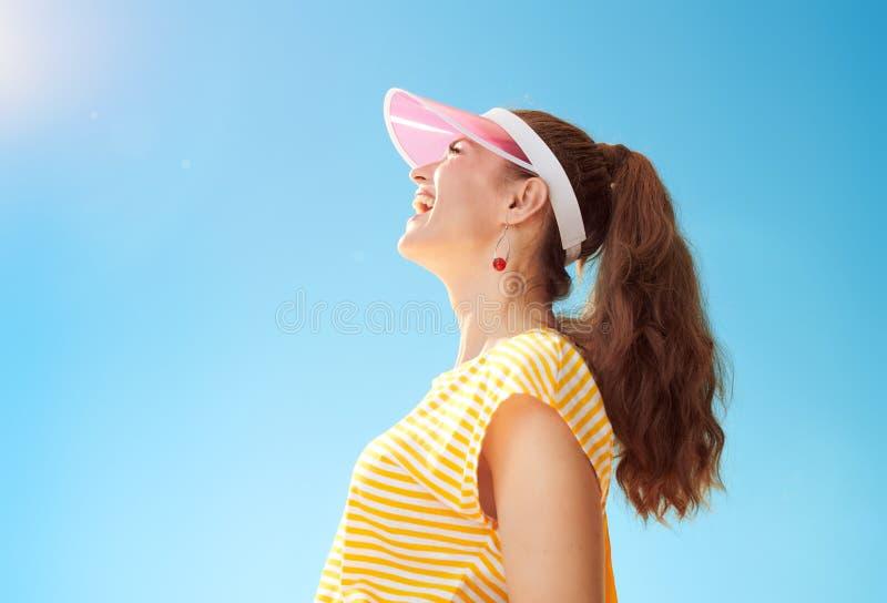 Glimlachende gezonde vrouw die tegen blauwe hemel omhoog exemplaarruimte bekijken royalty-vrije stock afbeeldingen