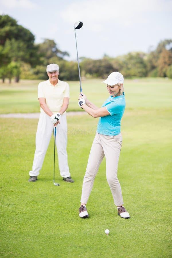 Glimlachende golfspelervrouw die schot nemen stock fotografie