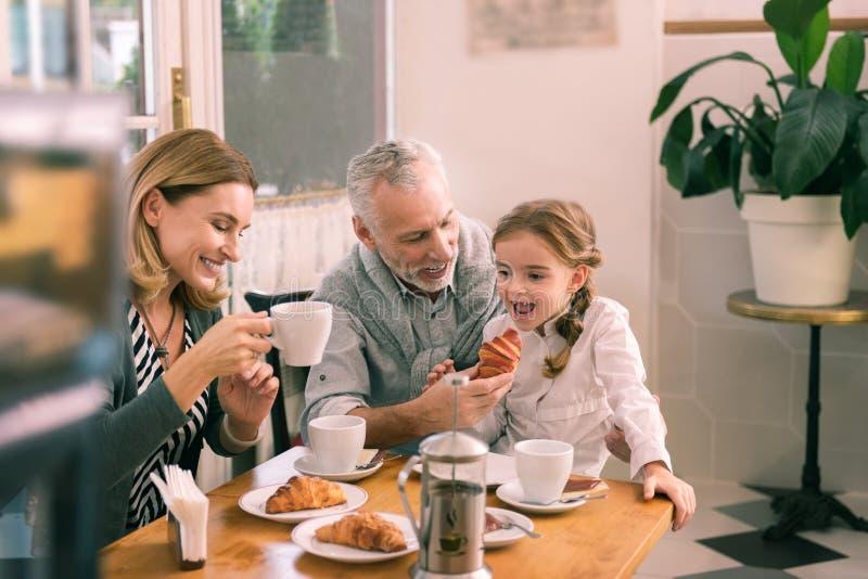 Glimlachende grijs-haired grootvader die croissant zijn meisje geven stock foto's