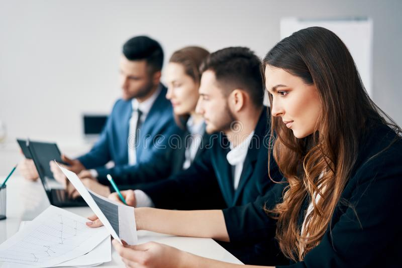 Glimlachende groep bedrijfsmensen die in rij samen bij lijst in modern bureau zitten stock afbeeldingen