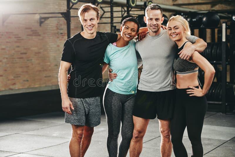 Glimlachende groep diverse vrienden die zich in een gymnastiek bevinden stock afbeeldingen