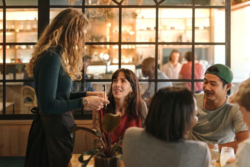 Glimlachende groep vrienden die tot voedsel in een bistro opdracht geven stock foto