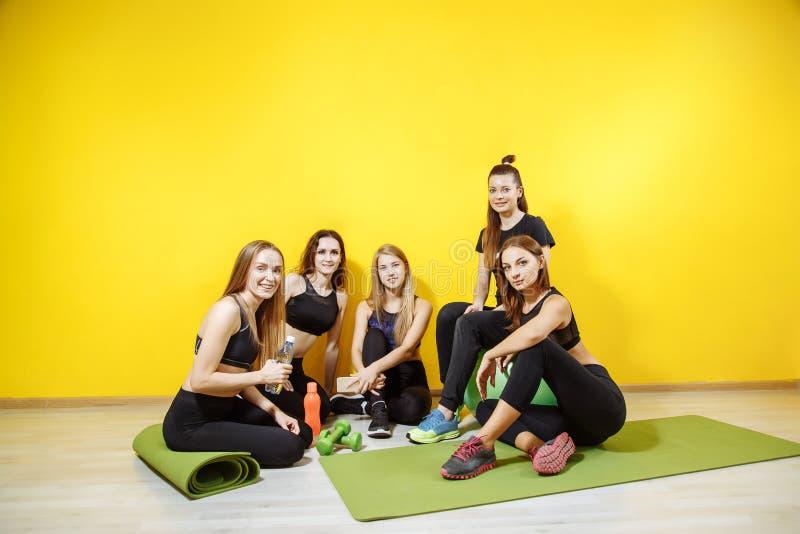 Glimlachende groep vrienden in sportkleding die tijdens rust in een gymnastiek lachen stock foto's