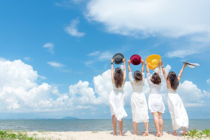 Glimlachende groepsvrouw die zomer dragen die van de manier de witte kleding op het zandige oceaanstrand, mooie blauwe hemelachte stock fotografie