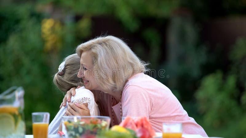 Glimlachende grootmoeder die emotioneel kleine kleindochter, gelukemotie omhelzen stock foto's