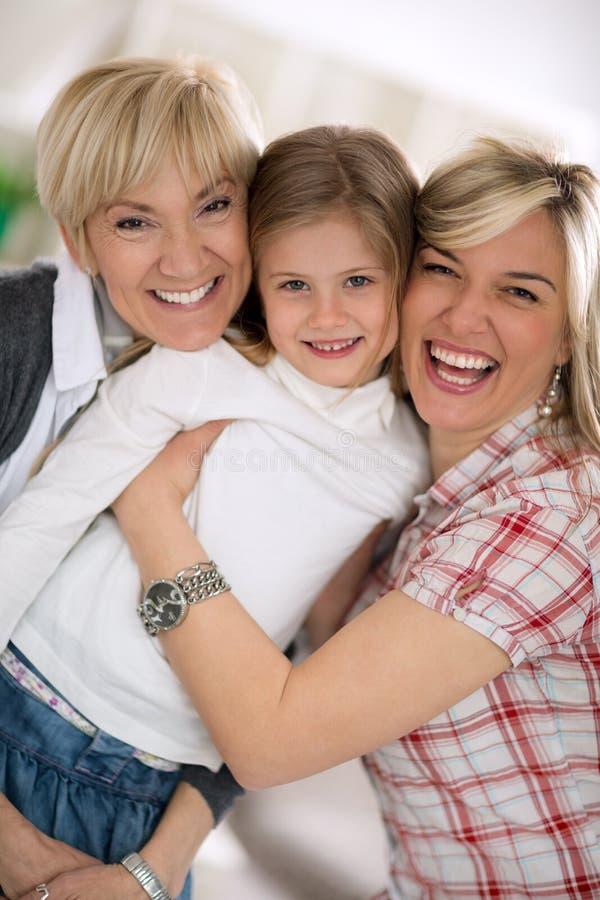 Glimlachende grootmoeder en moeder die meisje omhelzen royalty-vrije stock foto's