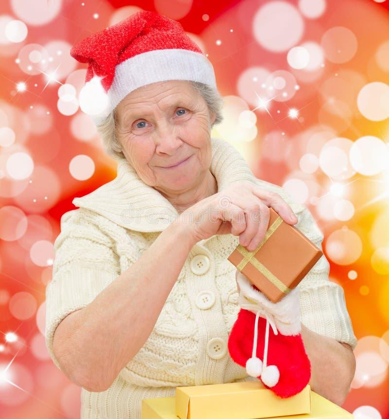 Glimlachende grootmoeder in Kerstman GLB stock fotografie