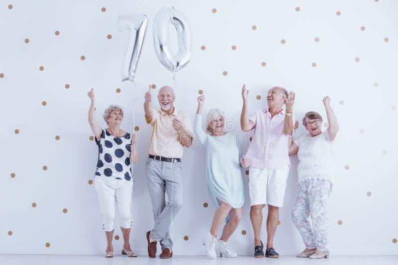 Glimlachende grootouders die vrienden` s van verjaardag genieten stock afbeelding