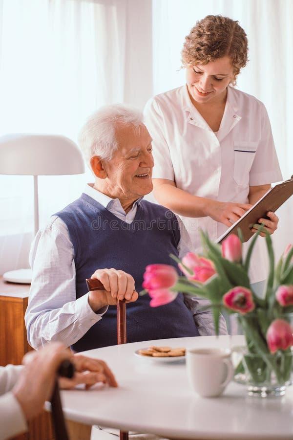 Glimlachende grootvader die over zijn dagprogramma spreken met een verpleegster in pensioneringshuis stock fotografie