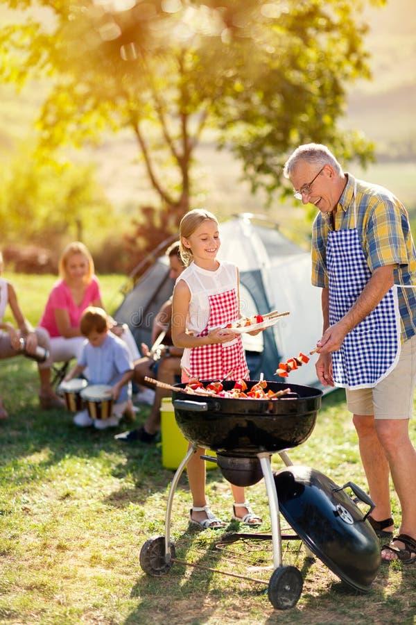 Glimlachende grootvader en kleindochter die barbecue roosteren royalty-vrije stock afbeelding