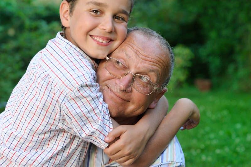 Glimlachende grootvader en kleinzoon stock foto's
