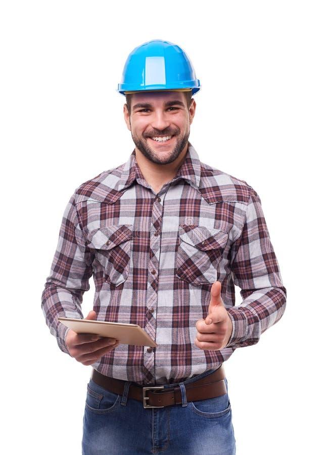Glimlachende handarbeider in blauwhelm met digitale tablet stock foto