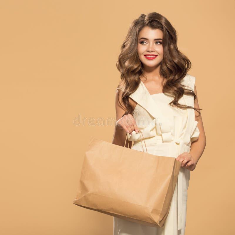 Glimlachende het document van de vrouwenholding het winkelen zak Gele achtergrond royalty-vrije stock foto's