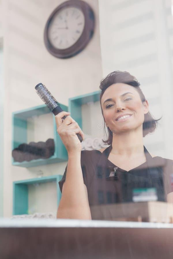Glimlachende het haarborstel van de kapperholding stock afbeeldingen